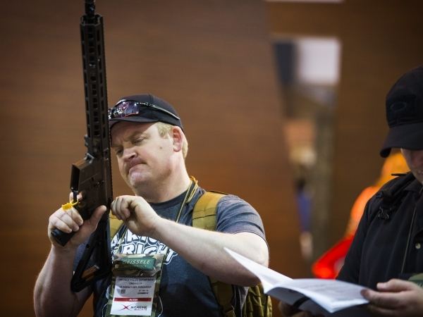 A man checks out at gun at the Geissele Automatics booth during the Shot Show at the Sands Expo on Tuesday, Jan. 19, 2016. Jeff Scheid/Las Vegas Review-Journal Follow @jlscheid