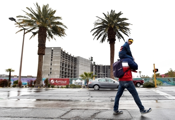 A man carries a boy as they walk along Las Vegas Boulevard near Riviera Boulevard across from the Resorts World construction site Tuesday, Jan. 19, 2016, in Las Vegas. David Becker/Las Vegas Revie ...