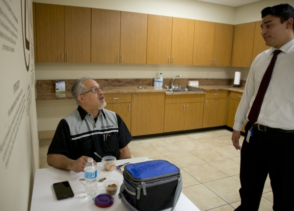 Kenny Kamae, a service technician at Lexus of Henderson in the Valley Automall, left, speaks with Gerrit Cuellar while eating a lunch he carefully portioned and selected to help control his high b ...