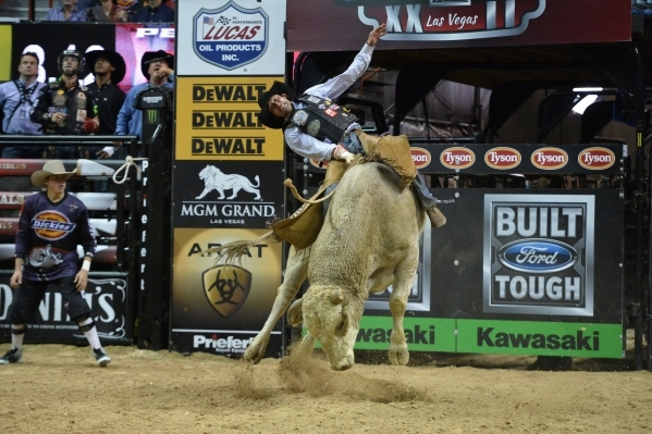 Ben Jones rides a bull during the 2015 PBR World Finals at the Thomas & Mack Center on Sunday, Oct. 25, 2015. Jones had to be back boarded out of the arena after being thrown off and trampled. ...