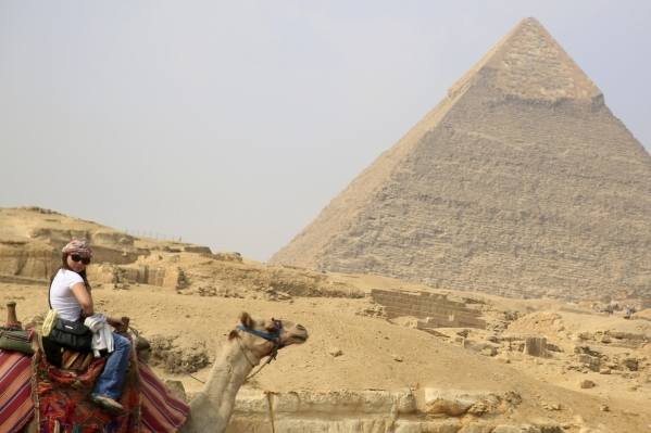 A tourist rides a camel in front of the Giza pyramids on the outskirts of Cairo. AMR ABDALLAH DALSH/REUTERS
