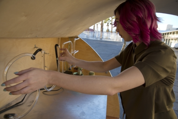 Victoria Hogan, the owner of Flora Pop, a traveling pop-up wedding company, carefully removes a neon sign from the back of the custom-built trailer she uses for ceremonies in the Holiday House Mot ...