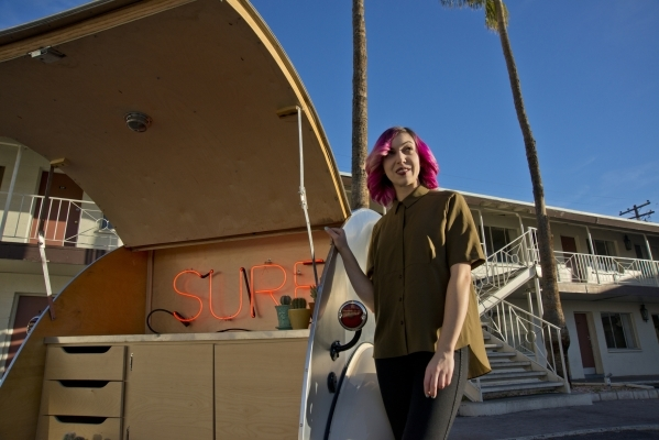 Victoria Hogan, the owner of Flora Pop, a traveling pop-up wedding company, poses for a photograph with the custom-built trailer she uses for ceremonies in the Holiday House Motel parking lot on L ...