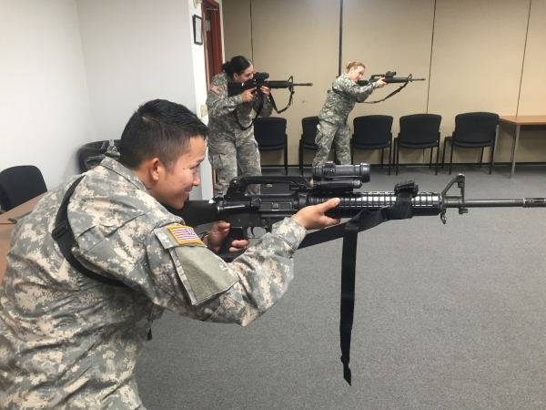 Pfc. Alyssa Patiga, 26, of Reno, with other soldiers from the Nevada Army National Guard's 422nd Expeditionary Signal Battalion aim their weapons during a room-clearing drill, Thursday, Jan. ...