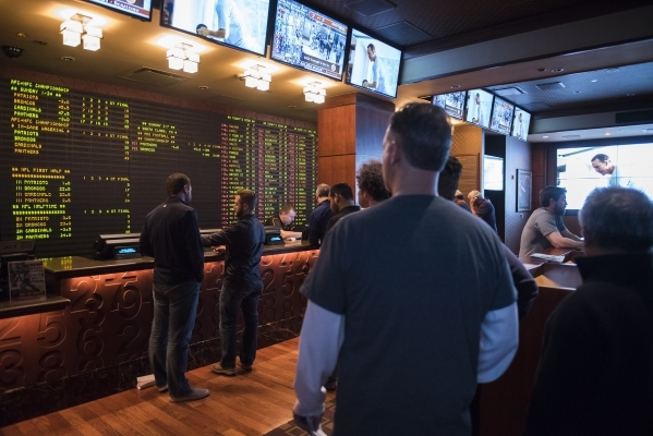 Gamblers prepare to make bets as the opening line of the Super Bowl is placed at the Golden Nugget hotel-casino sports book in Downtown Las Vegas on Sunday Jan 24, 2015. The Carolina Panthers are  ...