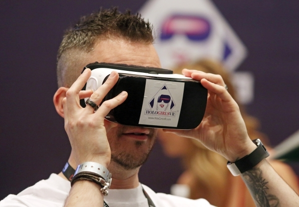 Show exhibitor Ed Collins looks through a device that allows the view to see virtual reality pornography at the Holo Film Productions booth during the AVN Adult Entertainment Expo 2016 at Hard Roc ...