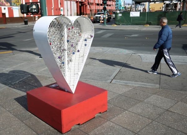 A pedestrian walks past the now-fixed Love Locket sculpture in downtown Las Vegas on Friday, Jan. 22, 2016. According to Downtown Project spokeswoman Maria Phelan, security  footage shows a couple ...