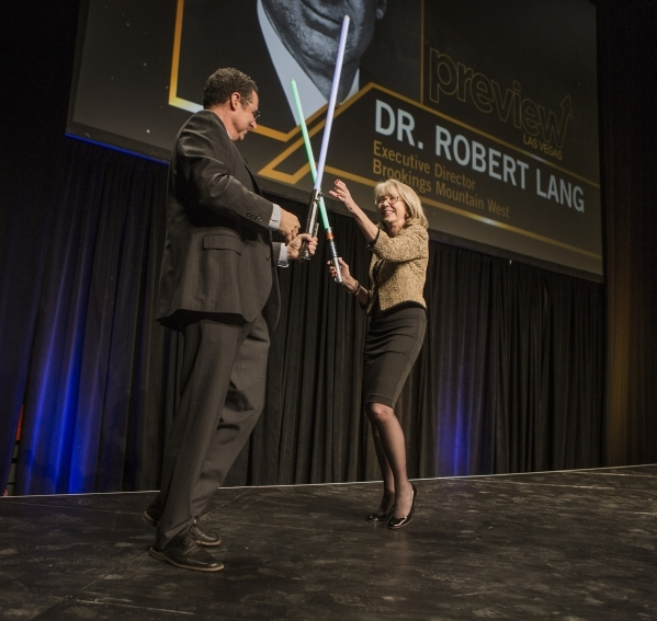 Dr. Rob Lang, left, executive director, Brookings West, and Kristin McMillan, president and CEO of the Las Vegas Metro Chamber duels with sabers during Preview at the Cox Pavilion on the UNLV Camp ...