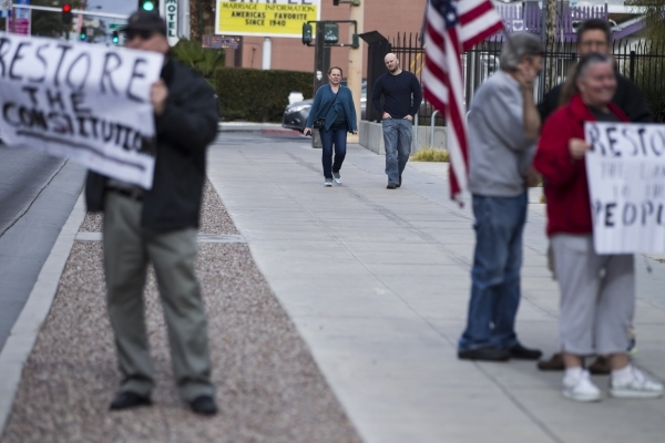 """Passerby walk near supporters of the Bundy family during a rally in support of what they call """"victims of federal oppression"""" outside of the Lloyd George U.S. Courthouse on Saturday, Jan ..."""