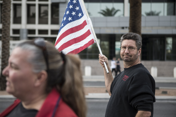 """Greg Whalen holds up an American flag during a rally in support of what they call """"victims of federal oppression"""" outside of the Lloyd George U.S. Courthouse on Saturday, Jan. 23, 2016,  ..."""