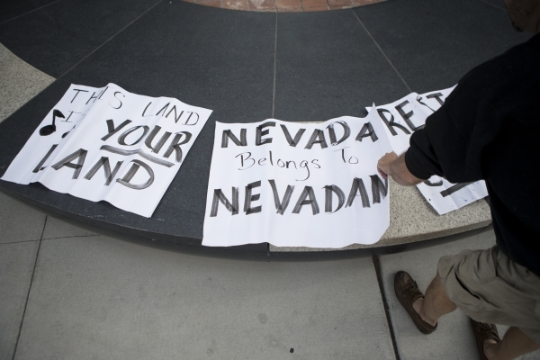 """Greg Whalen picks up a sign during a rally in support of what they call """"victims of federal oppression"""" outside of the Lloyd George U.S. Courthouse on Saturday, Jan. 23, 2016, in Las Veg ..."""