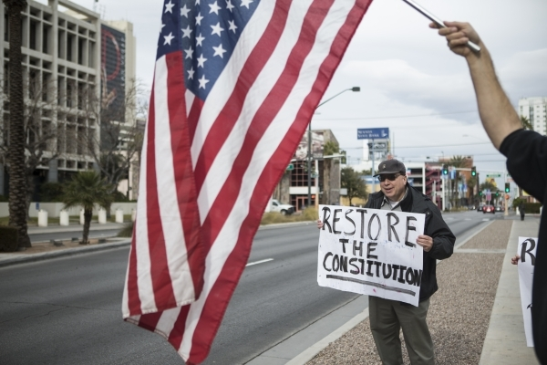 """Leo Martinez, supporter of the Bundy family, holds up a sign during a rally in support of what they call """"victims of federal oppression"""" outside of the Lloyd George U.S. Courthouse on Sa ..."""