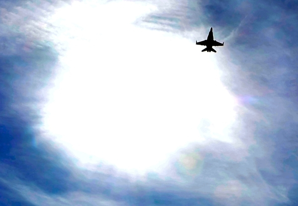 An F-16 fighter jet is silhouetted as it passes by the sun after taking off from Nellis Air Force Base during a Red Flag exercise on Monday, Jan. 25, 2016, in Las Vegas. More than 80 warplanes fro ...