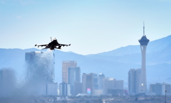 An F-16 fighter jet with its after-burner aglow takes off from Nellis Air Force Base during the year's first Red Flag exercise on Monday, Jan. 25, 2016, in Las Vegas. More than 80 warplanes  ...