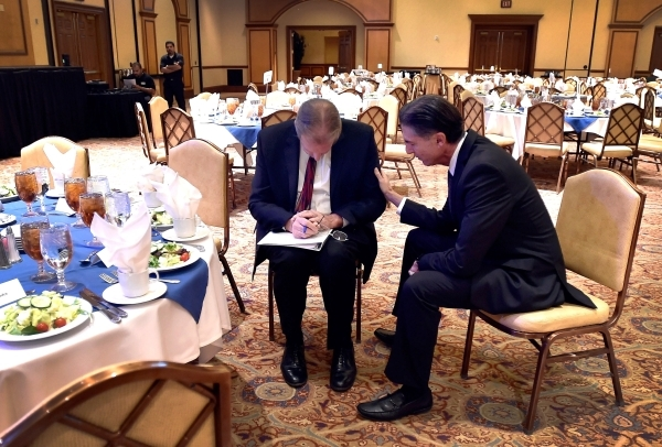 North Las Vegas Mayor John Lee, left, and Communications Director Mitch Fox pray before Lee's State of the City address at the Texas Station hotel-casino on Thursday, Jan. 28, 2016, in North ...