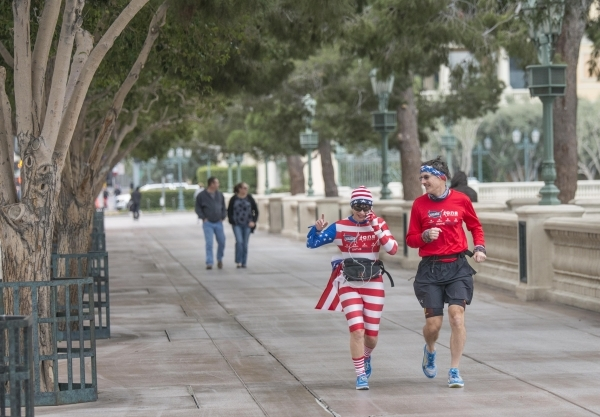 """Helene Neville, left, runs between the South Strip """"Welcome to Las Vegas"""" sign and downtown's """"Welcome to Las Vegas"""" sign on Friday, Jan. 29, 2016. She was joined on the  ..."""