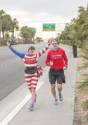 """Helene Neville, left, raises her arms as she runs between the South Strip """"Welcome to Las Vegas"""" sign and downtown's """"Welcome to Las Vegas"""" sign on Friday, Jan. 29, 2016. ..."""