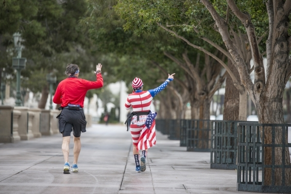 """Helene Neville, right, points as she runs between the South Strip """"Welcome to Las Vegas"""" sign and downtown's """"Welcome to Las Vegas"""" sign on Friday, Jan. 29, 2016. She was ..."""