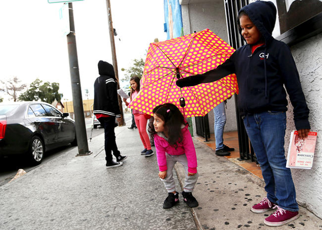 Valeria Villanueva holds an umbrella for Joselyn Juarez while they wait for a church service outside St. Joseph's Catholic Church in downtown Las Vegas on Sunday, Jan. 31, 2016. (Rachel Asto ...
