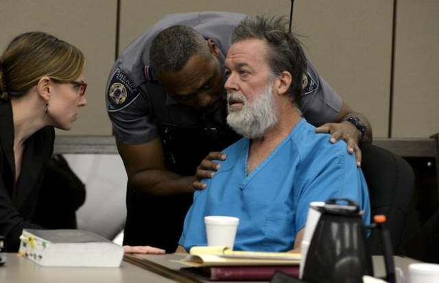 A deputy tries to calm Robert Lewis Dear, 57, accused of shooting three people to death and wounding nine others at a Planned Parenthood clinic in Colorado last month, as he spoke out at his heari ...