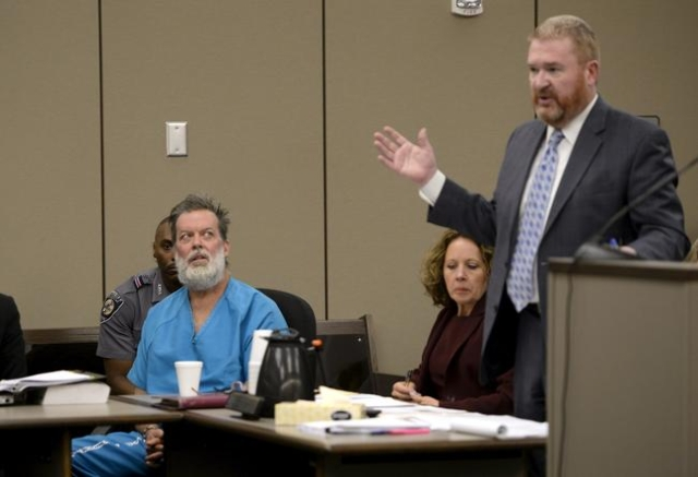 Robert Lewis Dear, 57, accused of shooting three people to death and wounding nine others at a Planned Parenthood clinic in Colorado last month, looks at his defense attorney Dan King during his h ...