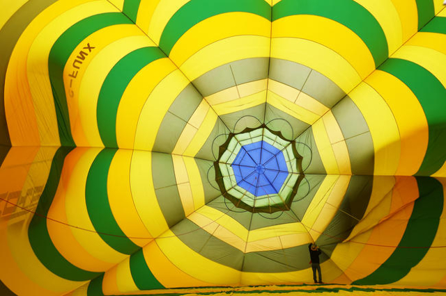 """Pilot Cliff Skocdopole checks the inside of his balloon """"Mr. Smee"""" before lifting off during the annual Hot Air Balloon Festival Saturday, Jan. 23, 2016, in Mesquite, Nev. The festival,  ..."""