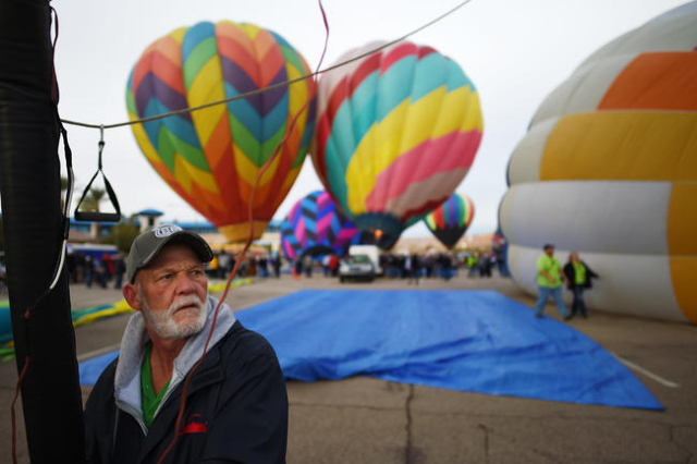 """David Campbell keeps an eye on other balloons while helping launch the balloon """"Mr. Smee"""" during the annual Hot Air Balloon Festival Saturday, Jan. 23, 2016, in Mesquite, Nev. The festiv ..."""