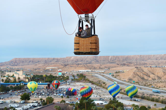 Balloons float over Interstate 15 after lifting off across from the CasaBlanca Resort during the annual Hot Air Balloon Festival Saturday, Jan. 23, 2016, in Mesquite, Nev. The festival, about 80 m ...