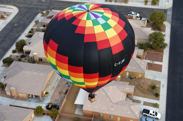 A hot air balloon floats over a neighborhood during the annual Hot Air Balloon Festival Saturday, Jan. 23, 2016, in Mesquite, Nev. The festival, about 80 miles north of Las Vegas, continues throug ...