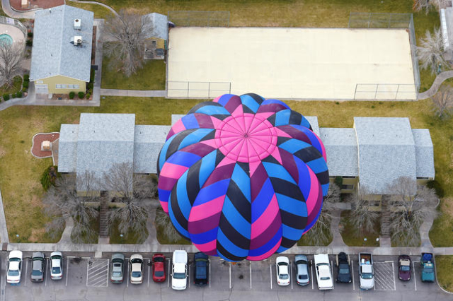A hot air balloon floats over an apartment complex during the annual Hot Air Balloon Festival Saturday, Jan. 23, 2016, in Mesquite, Nev. The festival, about 80 miles north of Las Vegas, continues  ...