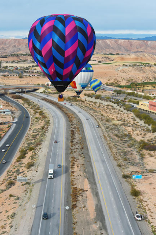Hot air balloons float over Interstate 15 during the annual Hot Air Balloon Festival Saturday, Jan. 23, 2016, in Mesquite, Nev. The festival, about 80 miles north of Las Vegas, continues through S ...