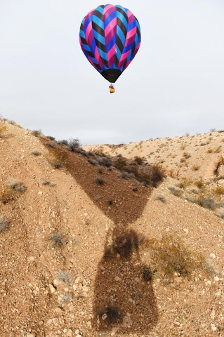 Hot air balloons float over the desert landscape during the annual Hot Air Balloon Festival Saturday, Jan. 23, 2016, in Mesquite, Nev. The festival, about 80 miles north of Las Vegas, continues th ...
