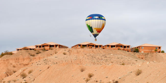 A hot air balloon passes over a residential development during the annual Hot Air Balloon Festival Saturday, Jan. 23, 2016, in Mesquite, Nev. The festival, about 80 miles north of Las Vegas, conti ...