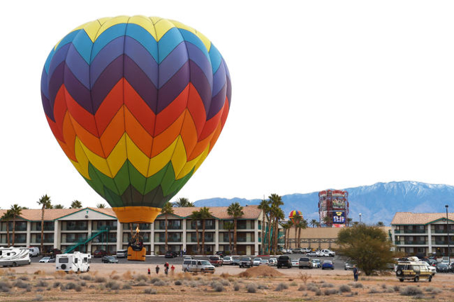 A hot air balloon comes in for a landing in the parking lot of the Eureka Casino Resort during the annual Hot Air Balloon Festival Saturday, Jan. 23, 2016, in Mesquite, Nev. The festival, about 80 ...