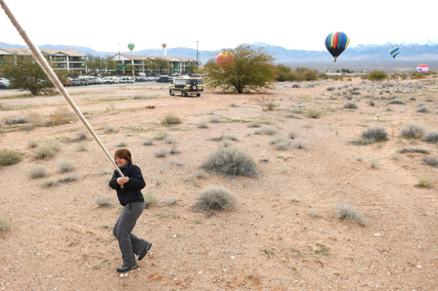 Sheri Skocdopole helps guide a hot air balloon to a landing in the parking lot of the Eureka Casino Resort during the annual Hot Air Balloon Festival Saturday, Jan. 23, 2016, in Mesquite, Nev. The ...