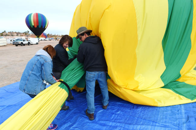 Sharon Campbell, Sheri Skocdopole and Cliff Skocdopole deflate a hot air balloon during the annual Hot Air Balloon Festival Saturday, Jan. 23, 2016, in Mesquite, Nev. The festival, about 80 miles  ...