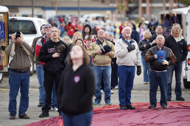 Balloonists and spectators listen to the national anthem as a balloon lifts off with a U.S. flag at the start of the annual Hot Air Balloon Festival Saturday, Jan. 23, 2016, in Mesquite, Nev. The  ...