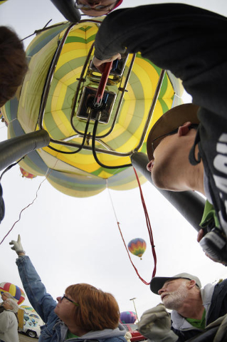 Sharon and David Campbell spot other balloons while pilot Cliff Skocdopole, right readies his balloon for take off during the annual Hot Air Balloon Festival Saturday, Jan. 23, 2016, in Mesquite,  ...