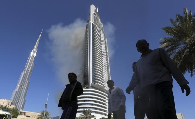 People walk as plumes of smoke rise from the 63-storey Address Downtown Dubai hotel and residential block, a day after it caught fire on New Year's Eve, in Dubai January 1, 2016. REUTERS/Str ...