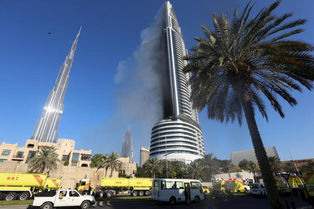 Plumes of smoke rise from the 63-storey Address Downtown Dubai hotel and residential block near the Burj Khalifa, the tallest building in the world, a day after the hotel caught fire on New Year&l ...