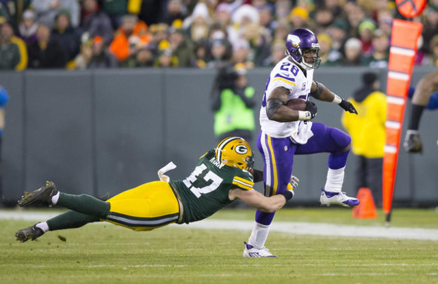 Jan 3, 2016; Green Bay, WI, USA; Minnesota Vikings running back Adrian Peterson (28) rushes with the football as Green Bay Packers linebacker Jake Ryan (47) defends during the second quarter at La ...