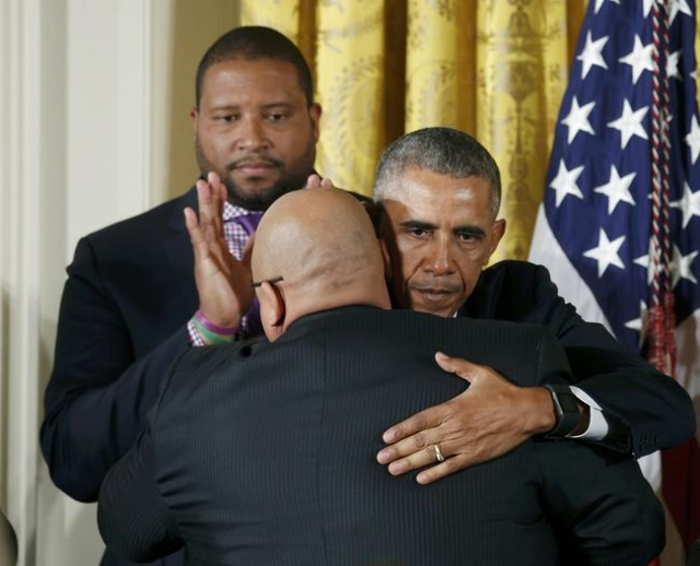 U.S. President Barack Obama (R) hugs an unidentified man after announcing steps the administration is taking to reduce gun violence while delivering a statement in the East Room of the White House ...