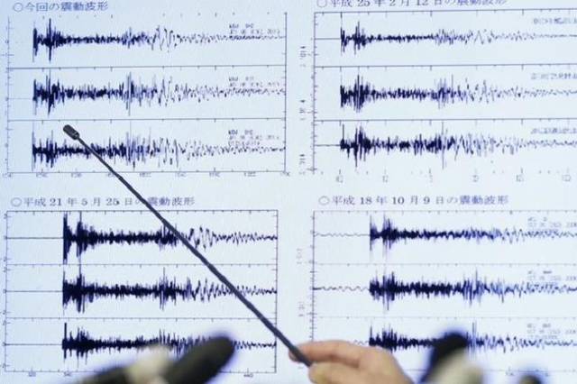 Japan Meteorological Agency's earthquake and tsunami observations division director Yohei Hasegawa points at a graph of ground motion waveform data observed today in Japan during a news conf ...