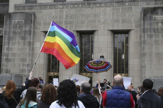 Supporters of same-sex marriage hold a rainbow flag and a rainbow umbrella outside Jefferson County Courthouse in Birmingham, Alabama February 9, 2015. (Marvin Gentry/Reuters)