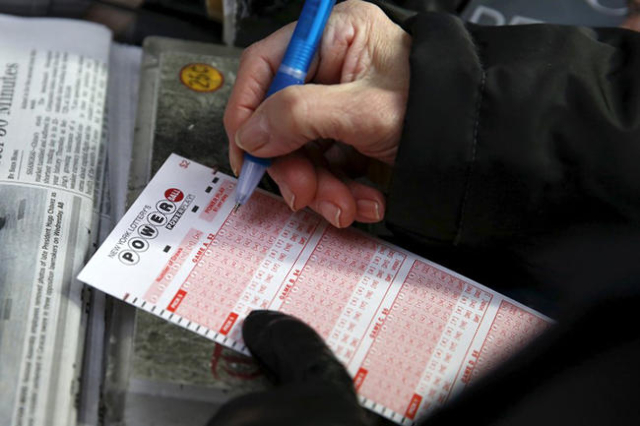 A woman fills out a ticket for the $700 million Powerball lottery draw at Times Square in the Manhattan borough of New York January 7, 2016. (Shannon Stapleton/Reuters)