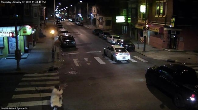 A still image from surveillance video shows a gunman (L) running away from a Philadelphia Police vehicle in which Officer Jesse Hartnett was shot shortly before midnight January 7, 2016 in Philade ...