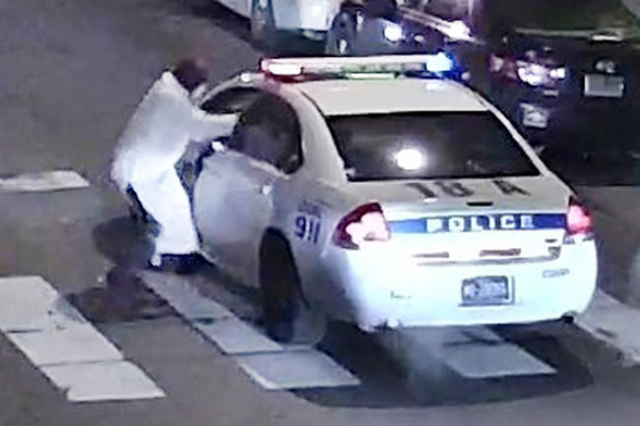 A still image from surveillance video shows a gunman (L) approaching a Philadelphia Police vehicle in which Officer Jesse Hartnett was shot shortly before midnight in Philadelphia, Pennsylvania th ...
