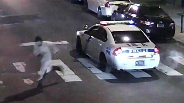 A still image from surveillance video shows a gunman (L) running away from a Philadelphia Police vehicle in which Officer Jesse Hartnett was shot in Philadelphia, Pennsylvania this Philadelphia Po ...