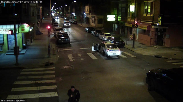 A still image from surveillance video shows Philadelphia Police Officer Jesse Hartnett (bottom C) chasing a gunman (not shown) after being shot in this Philadelphia Police Department image release ...