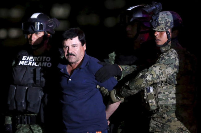 "Joaquin ""El Chapo"" Guzman is escorted by soldiers during a presentation at the hangar belonging to the office of the Attorney General in Mexico City, Mexico January 8, 2016. (Edgard Garr ..."